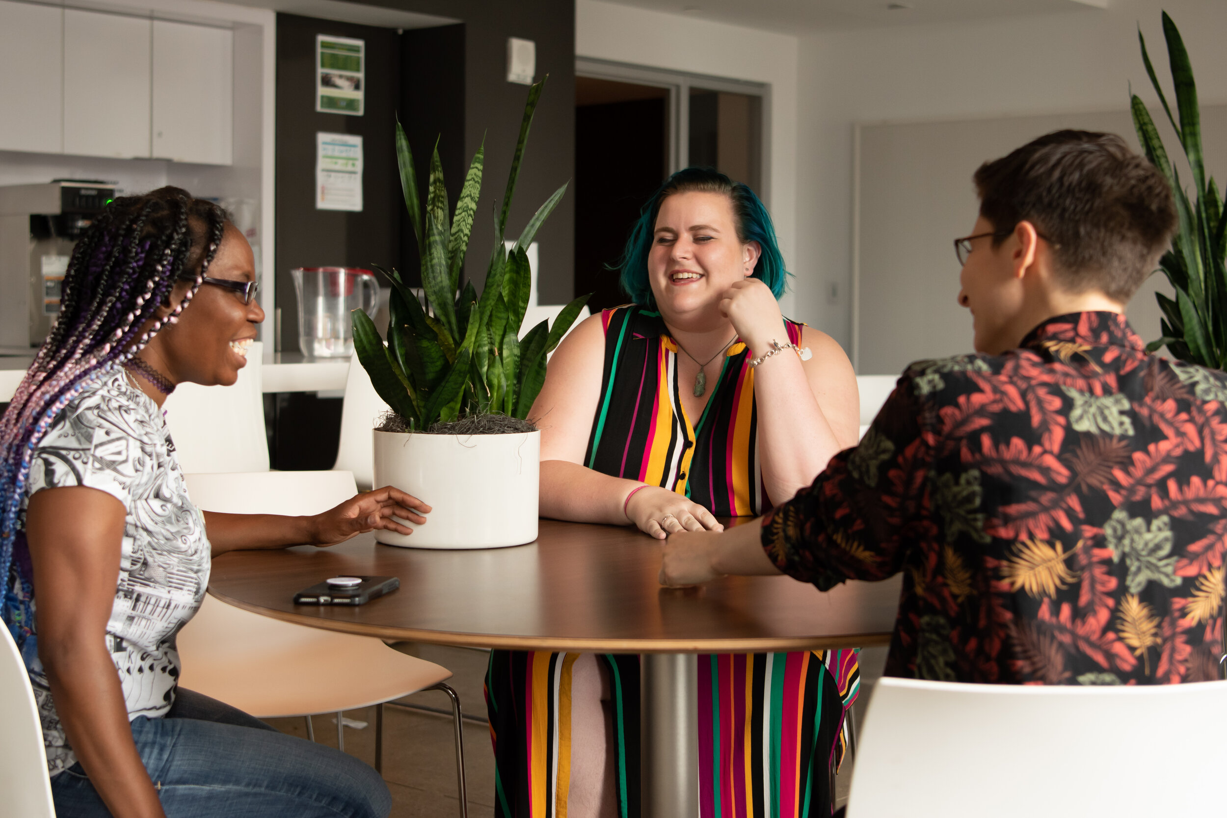 A group of two white people and one Black person sit laughing around a table. There is a plant and a phone on the table.