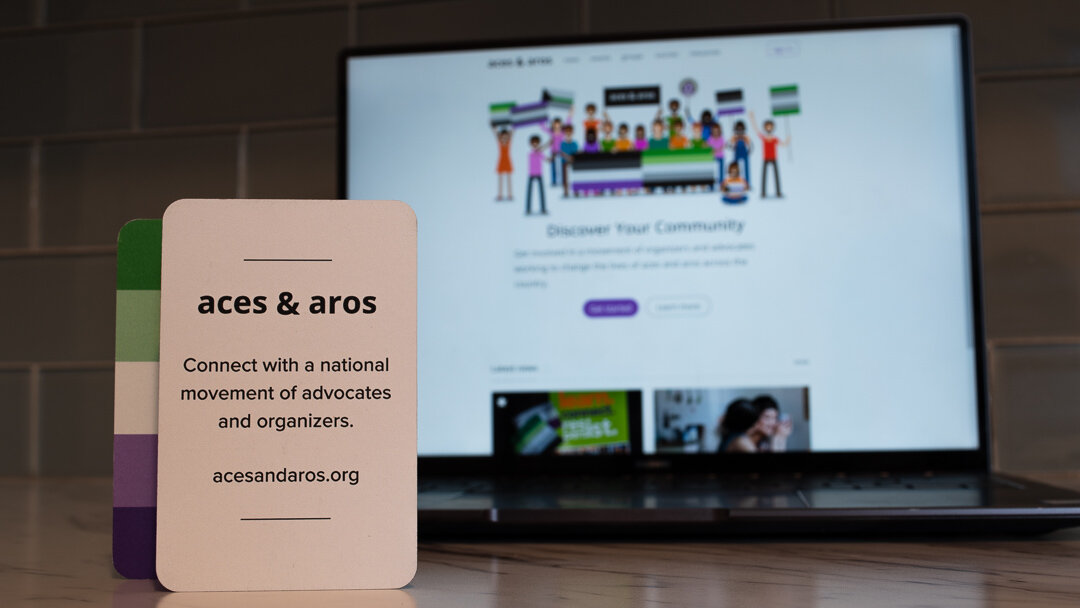 A card is propped in front of a computer screen. Both refer to the acesandaros.org website and show multiple a-spec pride flags.