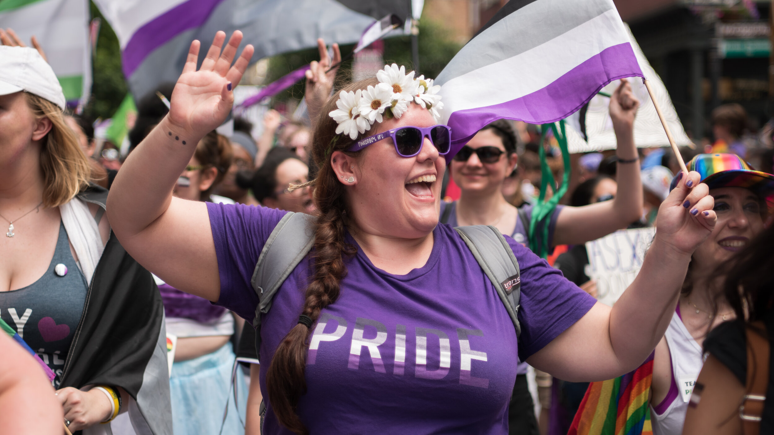 A person with a long brown braid in their hair is cheering and holding an ace flag in their right hand. They also have an ace pride shirt.